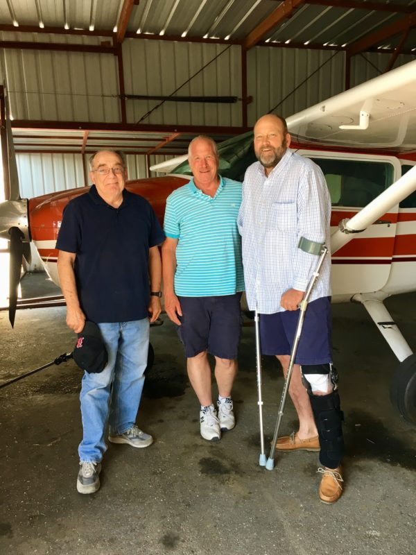 Pete with his buddies, Mike and Rex, in his hanger, next to his Cessna 182.